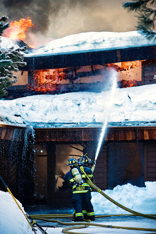 JEROME A. POLLOS/Press..North Lakes firefighters knock down flames on the upper level of a Twin Lakes Village home Tuesday. The fire, which was reported by a neighbor, gutted the home while the owners were at work. One of the homeowners did receive minor treatment at the scene for smoke inhalation after an unsuccessful attempt to rescue his dog. The cause of the fire hasn't been determined.