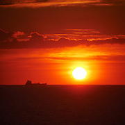 A ship moves across the glowing red disk of the setting sun as the Sun sets over the Irish Sea. In the middle of the Irish sea, on the Ferry from Wales to Dublin, as the sun sets on the horizon, and the sky turns a deep red.