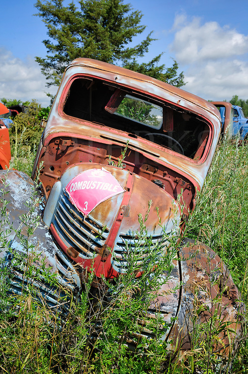 Very old and very crooked junkyard truck contemplates explosion with Combustable sticker on the hood.
