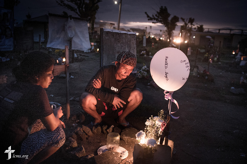 A man lights tends to memorial in a graveyard for victims of Typhoon Haiyan in Tacloban, Leyte Province, Philippines, on Friday, March 14, 2014. LCMS Communications/Erik M. Lunsford