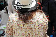 woman wearing a hat and flowery dress back view