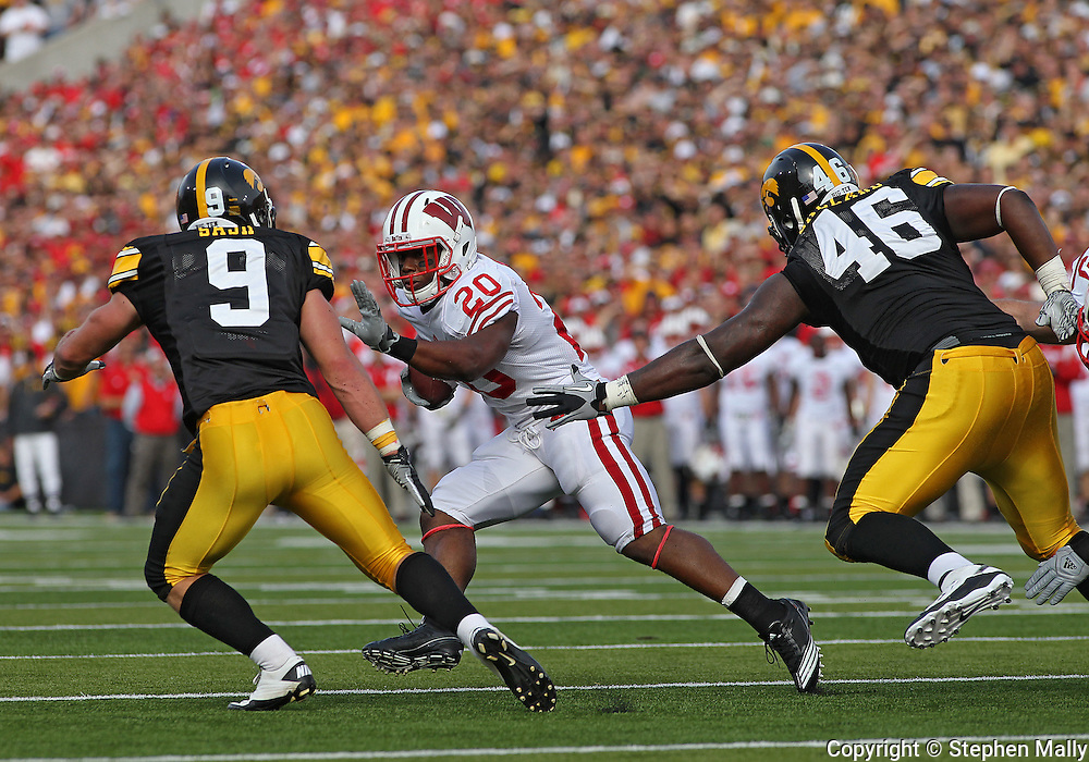 October 23 2010: Wisconsin Badgers running back James White (20) tries to avoid Iowa Hawkeyes cornerback Tyler Sash (9) and Iowa Hawkeyes defensive tackle Christian Ballard (46) during the first half of the NCAA football game between the Wisconsin Badgers and the Iowa Hawkeyes at Kinnick Stadium in Iowa City, Iowa on Saturday October 23, 2010. Wisconsin defeated Iowa 31-30.