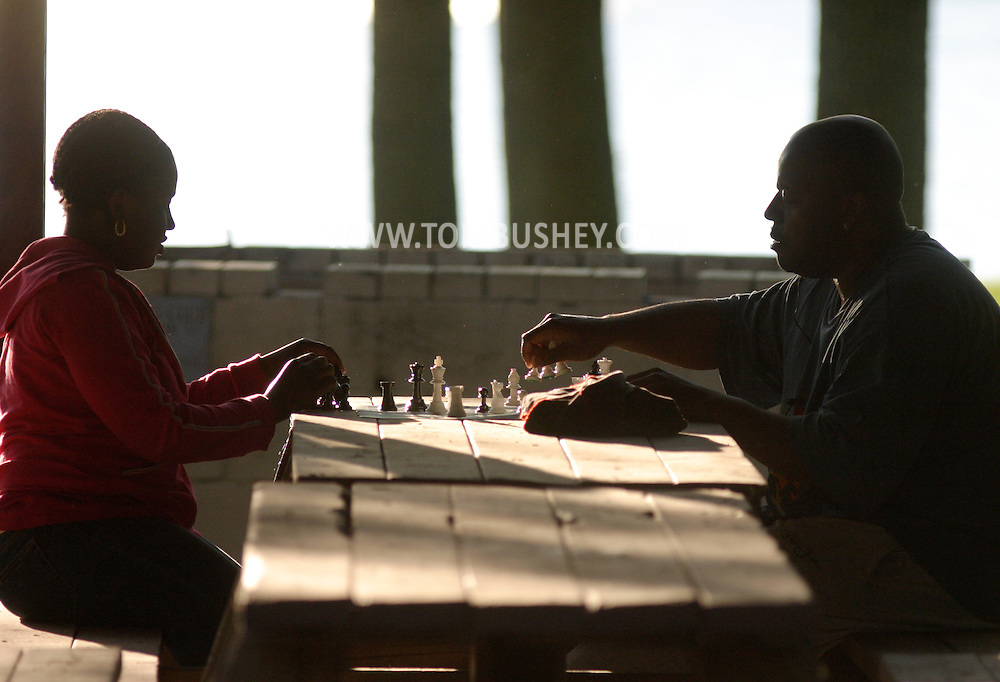 Middletown, N.Y. - A man and a teenager start to put away their chess pieces after playing a game at a picnic table in a pavillion at Fancher-Davidge Park on May 20, 2006. ©Tom Bushey