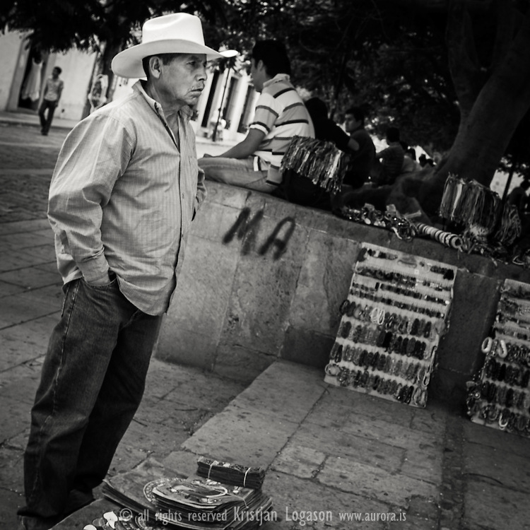 Man selling paintings on paper at the church square in Oaxaca