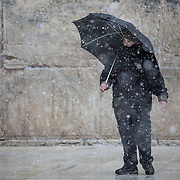 A man is seen on the plaza as snow and rain fall at The Western Wall on January 7, 2015 in Jerusalem, Israel. (Photo by Elan Kawesch)