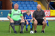 AFC Wimbledon manager Wally Downes sat on chair during the official team photocall for AFC Wimbledon at the Cherry Red Records Stadium, Kingston, England on 8 August 2019.