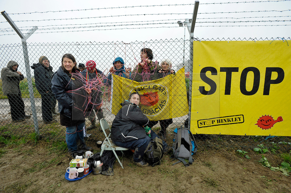 © Licensed to London News Pictures. 08/10/2012. Hinkley Point, Somerset, UK. Picture of protesters on both sides of the perimeter fence, as anti-nuclear campaigners hold a mass trespass protest at the site of Hinkley Point nuclear power station.  Energy company EDF plans to build a new nuclear power plant at the site called Hinkley C.  08 October 2012..Photo credit : Simon Chapman/LNP