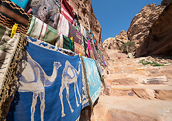 Detail of tourist gift stall with pashminas and other colourful woven local textiles at Petra, Jordan