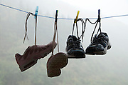shoes hanging to dry with in fog covered mountain in the background