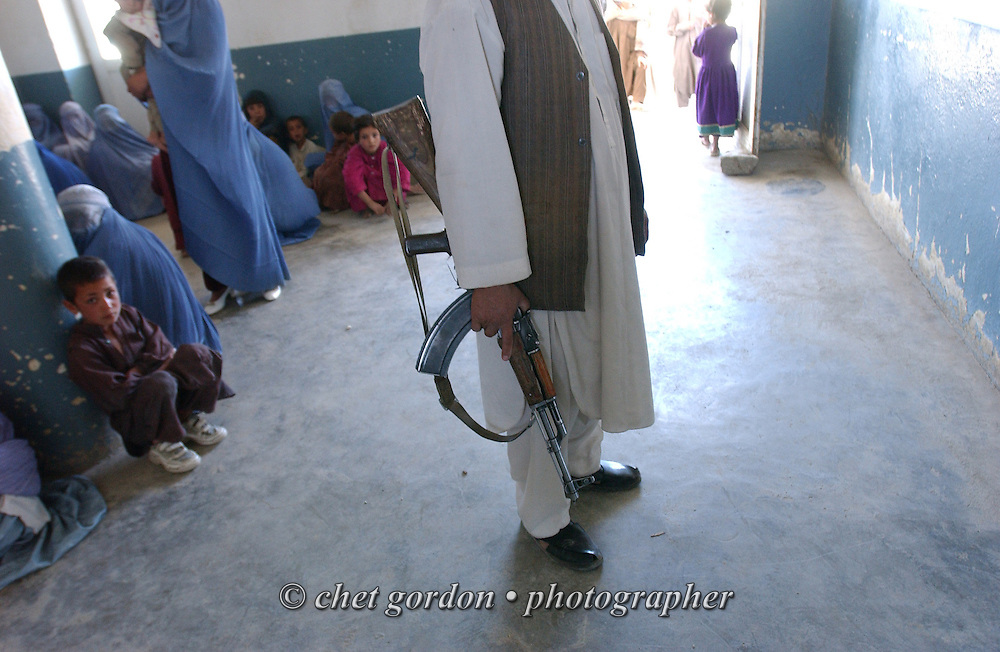 An Afghan man with an automatic weapon guards the waiting area of the Charasyab health clinic approximately 20 kilometers outside of Kabul, Afghanistan on Sunday, May 26, 2002.