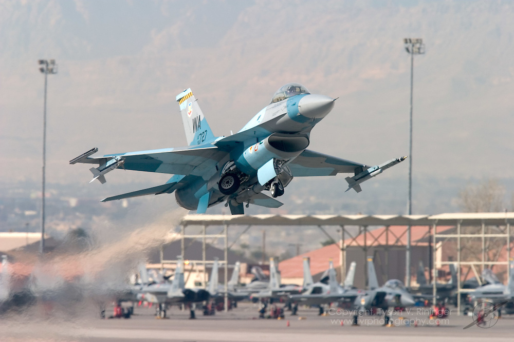 An adversary F-16 representing the Red Team blasts off from Runway 3L at Nellis AFB. In the background is just a small sample of the aircraft present during Red Flag Exercises.