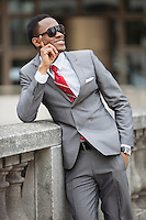 Happy young African American businessman wearing sunglasses