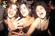 Three women smilling and with the same shirt dancing in a club and having fun. 2004