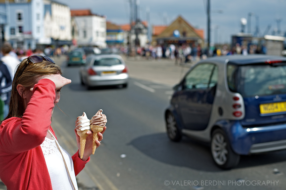 A girl waits in the sun for someone to arrive to enjoy her ice-cream. Scarborough, North Yorkshire. England. A pairwise selection to stimulate a reflection about the English seaside.