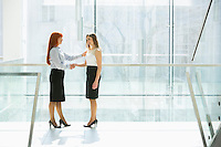 Full-length of businesswomen shaking hands at office hallway