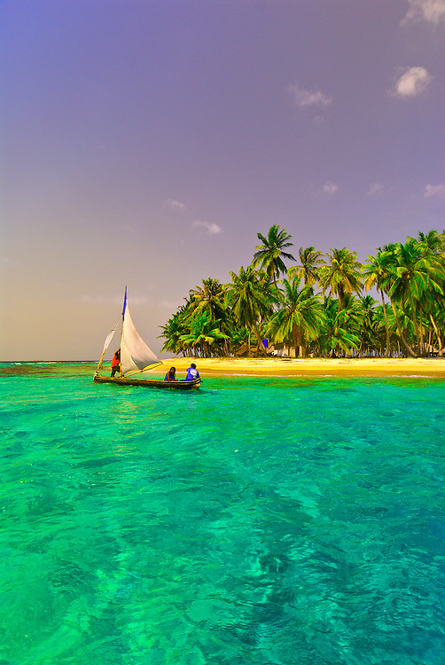 A Kuna Indian dugout canoe sailboat passes in front of the palm trees on Pelican Island (a.k.a. Icotupo Island), San Blas Islands (Kuna Yala), Caribbean Sea, Panama