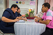 26 NOVEMBER 2012 - BANGKOK, THAILAND:  A man in pink (right) drops off a gift for the hospitalized King of Thailand at Siriraj Hospital in Bangkok. He was wearing pink because it's viewed as a fortuitous color that could bring the King better health. Siriraj was the first hospital in Thailand and was founded by King Chulalongkorn in 1888. It is named after the king's 18-month old son, Prince Siriraj Kakuttaphan, who had died from dysentery a year before the opening of the hospital. It's reported to one of the best hospitals in Thailand and has been home to Bhumibol Adulyadej, the King of Thailand, since 2009, when he was hospitalized to treat several ailments. Since his hospitalization tens of thousands of people have come to pay respects and offer get well wishes. The King's 85th birthday is on Dec 5 and crowds at the hospital are growing as his birthday approaches. The King is much revered throughout Thailand and is seen as unifying force in the politically fractured country.       PHOTO BY JACK KURTZ