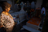 """A women watches her daughters decorate a family members grave with Cempasuchil (Marigold) Flowers which are traditionally used at a cemetery in the town of Zacapu, Michoacan, Mexico, on Nov. 2, 2011, as part of the celebration of the deceased life on """"Noche de Muertos"""" (Day of the Dead), a cheerful and solemn occasion. ..©Benjamin B Morris"""