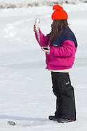 Middletown, New York - A girl looks at a fish she caught while ice fishing at the Shawangunk Fish and Game Association pond during the association's annual contest on Feb. 8, 2014. ©Tom Bushey / The Image Works