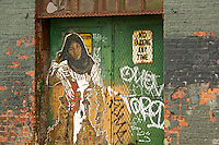 Street Art deplicting a muslim woman, in a doorway, New York City.