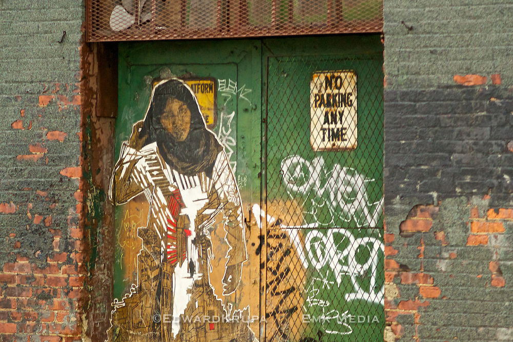 Street Art deplicting a muslim woman, in a doorway, New York City.