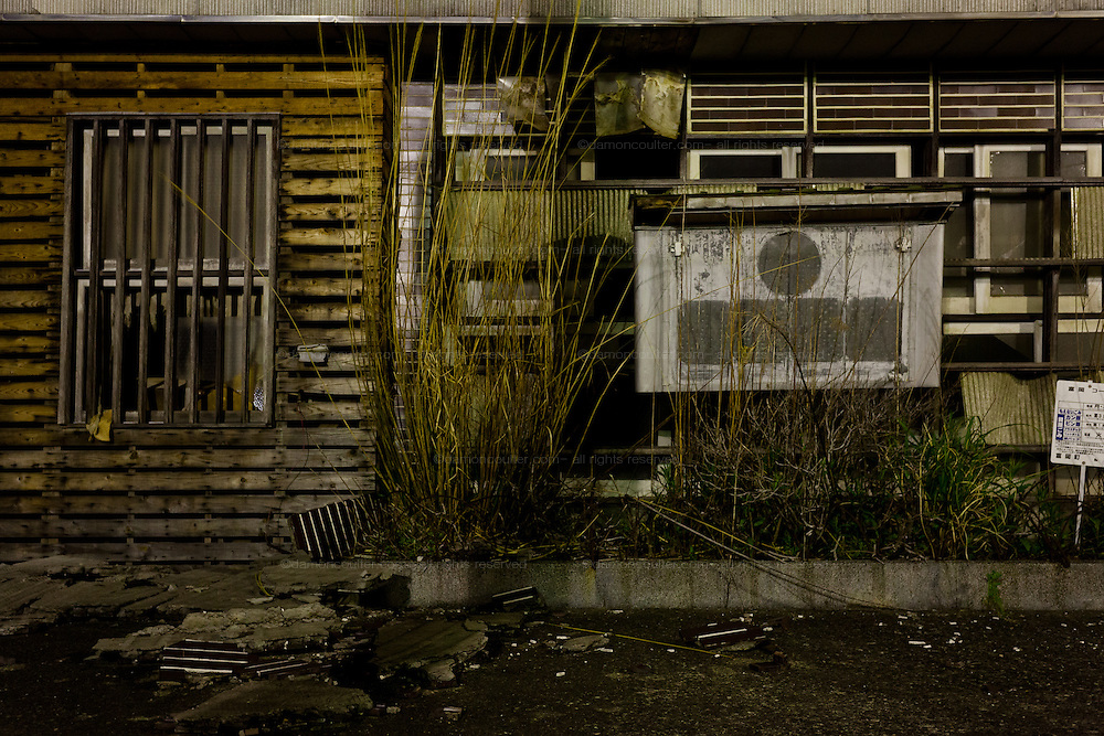 Empty streets and overgrown weeds at night in the town of Tomioka, Futaba District of Fukushima, Japan. Monday April 29th 2013. The town was evacuated on March 12th after the March 11th 2011 earthquake and tsunami cause meltdowns at the nearby Fukushima Daichi nuclear power station. It lies well within the 20 kms exclusion zone though parts of the town have recently been opened again to allow locals to visit their property during daylight hours.