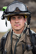 Fire fighter Steve Smith of Spring Valley Fire Department poses for a portrait as multiple fire departments, including Milpitas Fire Department, Spring Valley Fire Department, and Cal Fire, work to contain and extinguish a structure fire at the 3000 block of Calaveras Road near Spring Valley Golf Course in Milpitas, California, on February 10, 2014. (Stan Olszewski/SOSKIphoto)