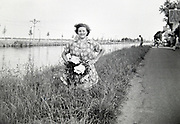 young adult woman posing with fresh picked wild flowers by canal Netherlands 1950s