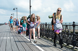 © Licensed to London News Pictures. 14/06/2014. Ryde, Isle of Wight, UK. Festival goers arrive at the Isle of Wight for the Isle of Wight Festival.The UK is experiencing a period of hot sunny weather with temperatures over the weekend expected to reach 74 F (23 C).  Photo credit : Richard Isaac/LNP