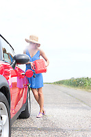 Full length of young woman refueling car on country road