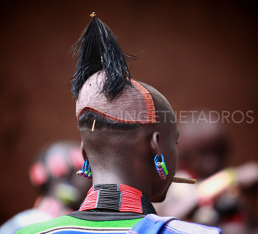 Hamar men wear clay hair buns representing killing of an enemy or a dangerous animal. The hairdo lasts up to one year. Above the forehead, a small holder is made to hold ostrich feathers.<br /> To protect their prized hairdos, Hamar men at all times carry with them a borkoto or carved wooden  stool which they use as a headrest. Exclusive at AuroraPhotos.<br /> http://www.auroraphotos.com/SwishSearch?Keywords=Ingetje+Tadros&amp;submit=Go!