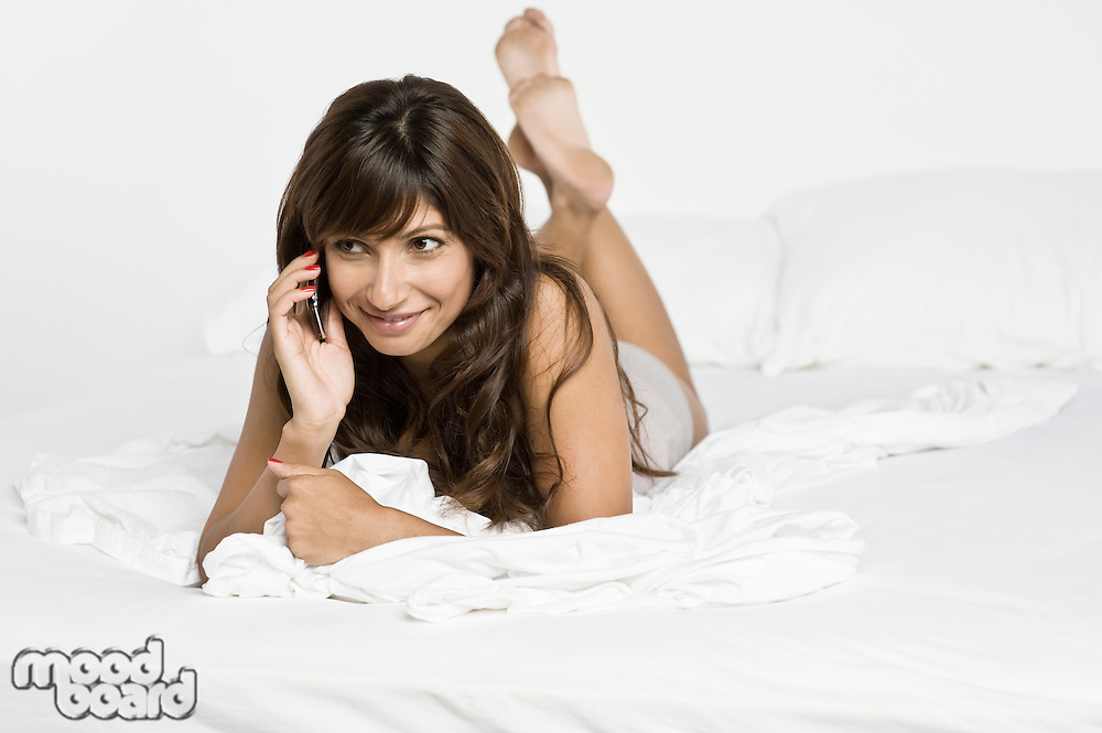 Mid adult woman lying on bed and talking on phone