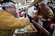 """A women buys  hand-made phallus-shaped lollipops during the Kanamara Festival in Kawasaki, Japan on 04 April 2010. The fertility festival, often just called the """"penis festival,"""" has been held since the early 1600s and also aims to promote awareness of AIDS and STDs. Around 4,000 of the lollipops were sold.."""