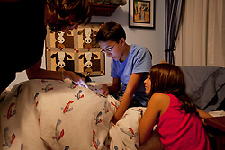 "Vanessa Gonzalez gets her children Andrea and Santiago ready for bed, Littleton, Colo., Aug. 29, 2011. Santiago, 13, is a full-time college student at the Colorado School of Mines, an engineering university. He wakes up at 5:30 a.m. every morning during the academic semester to develop iPad and iPhone applications in a programming language called Objective C, which he learned from a textbook when he was 9 years old. That textbook and 86 similar volumes including Applied Finite Mathematics, Infinity in Your Pocket, Programming in C++ and Dictionary of Physics, sit in a glass-fronted bookcase opposite his bed. ""Exceptionally gifted"" is the commonly used phrase for kids as smart as Gonzalez."