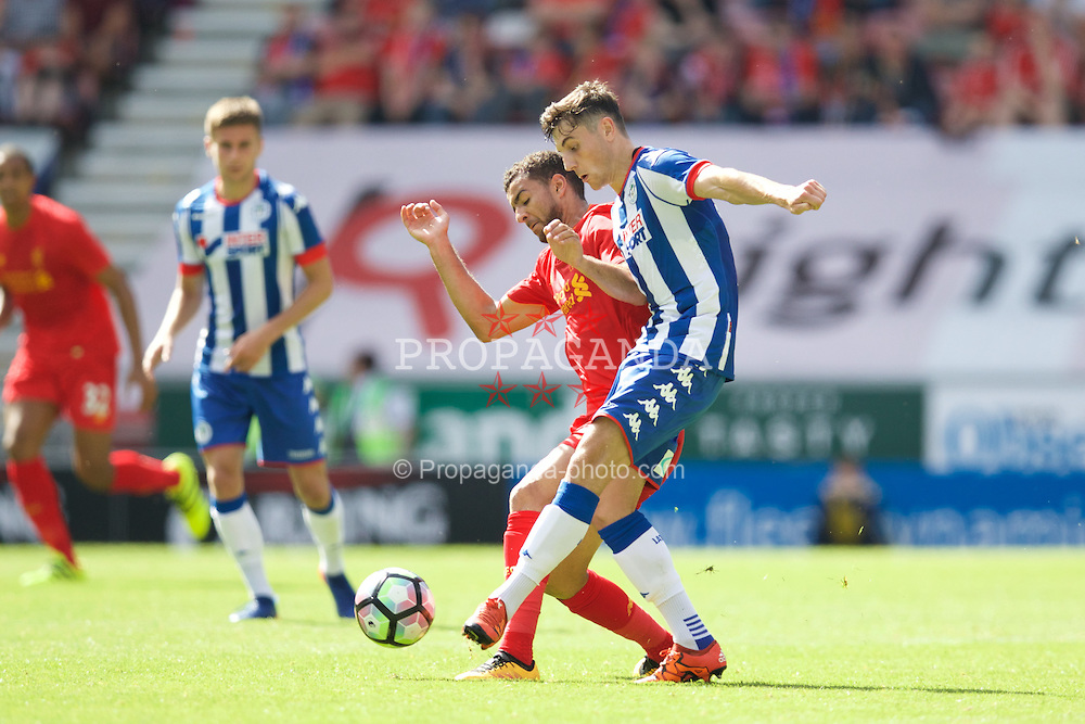 WIGAN, ENGLAND - Sunday, July 17, 2016: Liverpool's Kevin Stewart in action against Wigan Athletic's Jordan Flores during a pre-season friendly match at the DW Stadium. (Pic by David Rawcliffe/Propaganda)