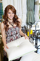 Portrait of beautiful young woman shopping for cushion in store