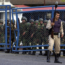 A Caracas Police officer stands guard, Dec. 16, 2002, outside  the Brigada Motorizada after Federal troops, behind fence, unsuccessfully attempted to commandeer the Police station in a tense standoff that pitted opponents and supporters of Chavez as well as National Guard and local police officers against each other.