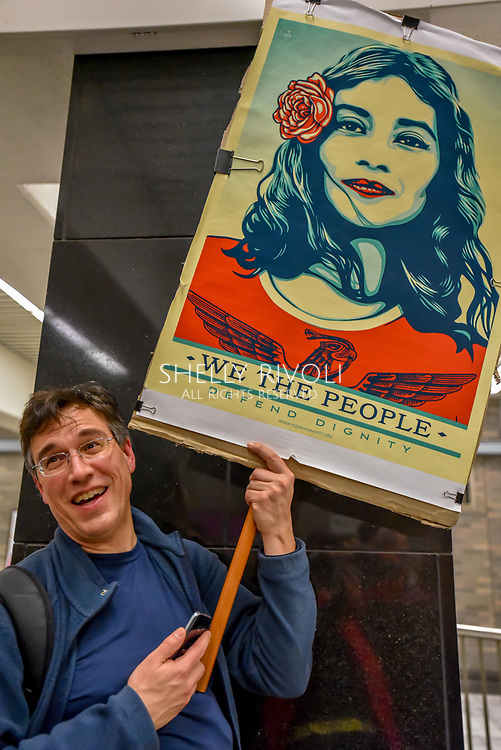 "San Francisco, California, USA. 21st January, 2017. Man holds sign ""We the people"" with image by artist Shepard Fairey in San Francisco BART station before women's march 2017. Credit: Shelly Rivoli"