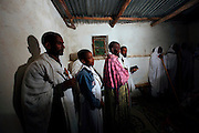 """A Baptism ceremony taking place in a church. Occupying a high plateau and bordering with Eritrea in the very north of Ethiopia lies the ancient Province of Tigray. It is an area widely considered to be the fulcrum of Ethiopian culture with towns dated to before the birth of Christ. Distinctively different from the rest of Ethiopia, strongly Orthodox Christian and culturally proud, Tigray is a mountainous and rocky region dotted with ancient churches carved in to sandstone cliffs. Filling these churches are old religious manuscripts and Bibles safe-guarded by protective Priests. Its remoteness has protected the culture as well as the religious sanctuaries that have been described as """"the greatest of the historical-cultural heritages of the Ethiopian people"""". But now Tigray is at a crossroads. Improved infrastructure has led to an opening up of even the remotest towns and villages. Signs of modernity such as internet cafes and cell phones are increasingly being used by younger Tigraians dressed in jeans and T-shirts. Yet the Church remains an ancient and powerful institution which protects its ancient customs creating scenes that haven't changed since Biblical times.."""