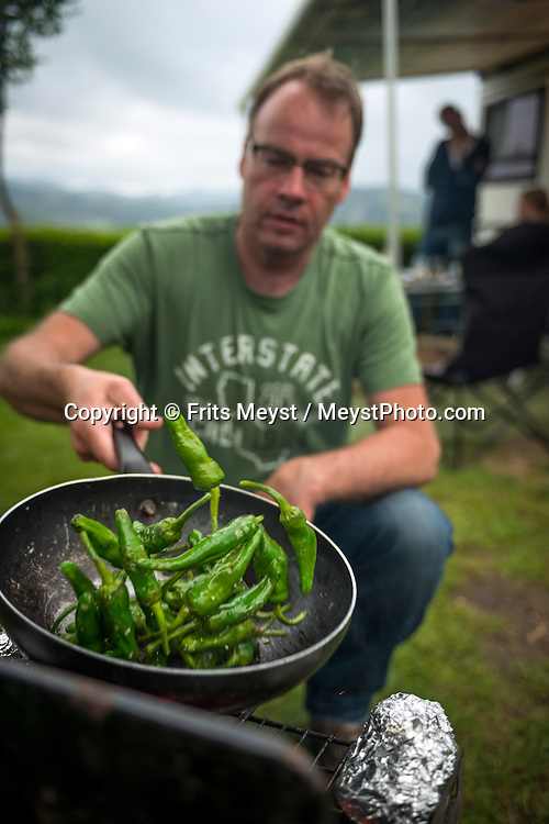 Zarautz, Gipuzkoa, Basque Country, Spain, June 2014. Green peppers. Champion amateur chef, Gaston Dolmans is cooking out with friends on Gran Camping Zarautz. The Basque Country (Basque: Euskadi, Spanish: Pais Vasco) is a region at the north of Spain, bordering the Atlantic Ocean and France. It is defined formally as an autonomous community of three provinces within Spain. Basque Country is one of the world's top gastronomic destinations. Photo by Frits Meyst / MeystPhoto.com