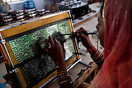An Indian student solders and assembles circuit boards in class in the Barefoot College in Tilonia village, Ajmer, Rajasthan, India. Photo by Suzanne Lee for Panos London