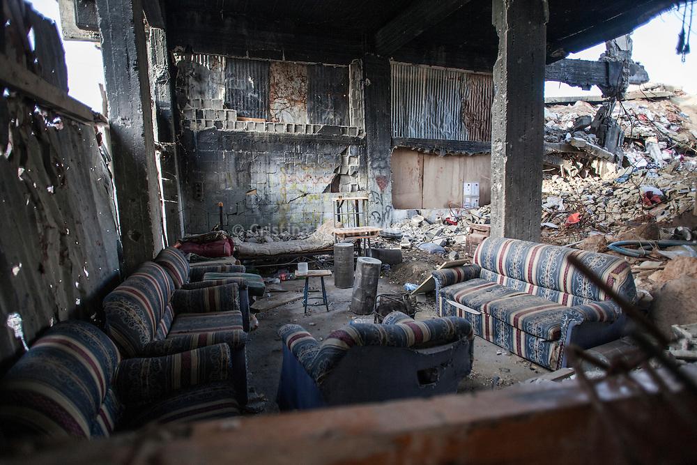 """Shejaya, quartiere a nord della striscia di Gaza. Una delle zone piu colpite dall'attacco israeliano """"Margine protettivo"""". Il quartiere è stato raso al suolo. La popolazione, a distanza di sei mesi dalla fine della guerra, vive tra le macerie della propria casa, al freddo, senza luce, gas e acqua. Nella foto all'interno di una casa distrutta, quello che rimane di un soggiorno."""