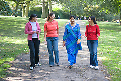 Four friends; walking in the park; talking,