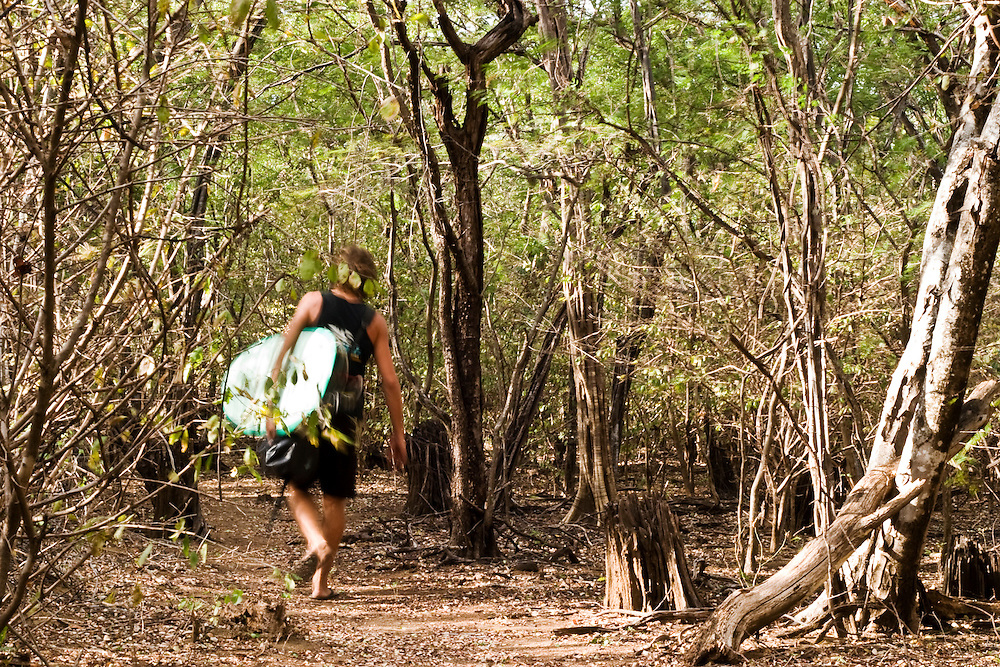 a surfer takes the wooded path to Witches rock which lies at the northern end of Playa Naranjo in the Santa Rosa National Park in Guanacaste, Costa Rica. Witches Rock is a world famous surf spot made famous by the movie, Endless Summer 2. The area is also famous as a staging post for arms being smuggled into Nicaragua by Oliver North.