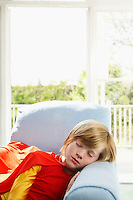 Young boy (7-9) sleeping in armchair wearing superhero costume indoors