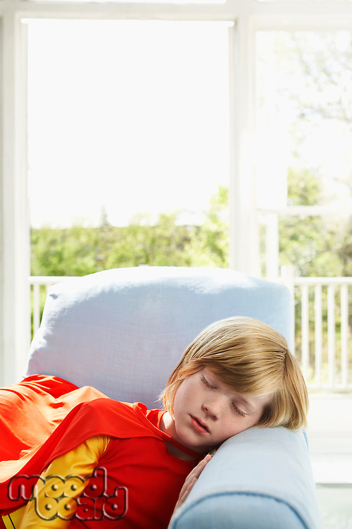 Young boy (7-9) sleeping in armchair wearing superhero costume indoors