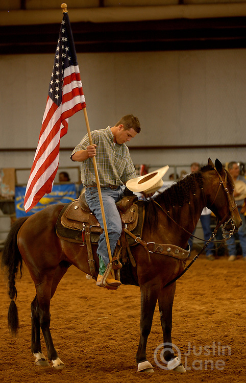 Cody Busby, 20, bows his head in prayer while holding an American flag at the start of rodeo night at the Cowboy Church in Amarillo, TX, Thursday July 14, 2005. The church rodeo, in which semi-professional bull riders compete, is designed to bring in people who are interested in the sport then expose them to the teachings of Jesus.