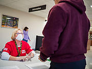 "18 MARCH 2020 - DES MOINES, IOWA: JOLYN CATALDO, a RN with the Polk County Department of Public Health, screens a person at the Polk County offices in downtown Des Moines before directing them to the proper office. The county reduced its services available to the public in order to reduce the number of people coming into county buildings. County workers are screening people coming into the building, asking about recent travel and health. On Wednesday morning, 18 March, Iowa reported 29 confirmed cases of the Coronavirus. Restaurants, bars, movie theaters, places that draw crowds are closed for at least 30 days. There are no ""shelter in place"" orders in effect anywhere in Iowa but people are being encouraged to practice ""social distancing"" and many businesses are requiring or encouraging employees to telecommute.       PHOTO BY JACK KURTZ"