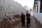 Young Buddhist monks walk through the streets of the Rabgya monestary in Golok region, Tibet (Qinghai, China). The monestary is home to around 500 monks of the Gelukpa sect.