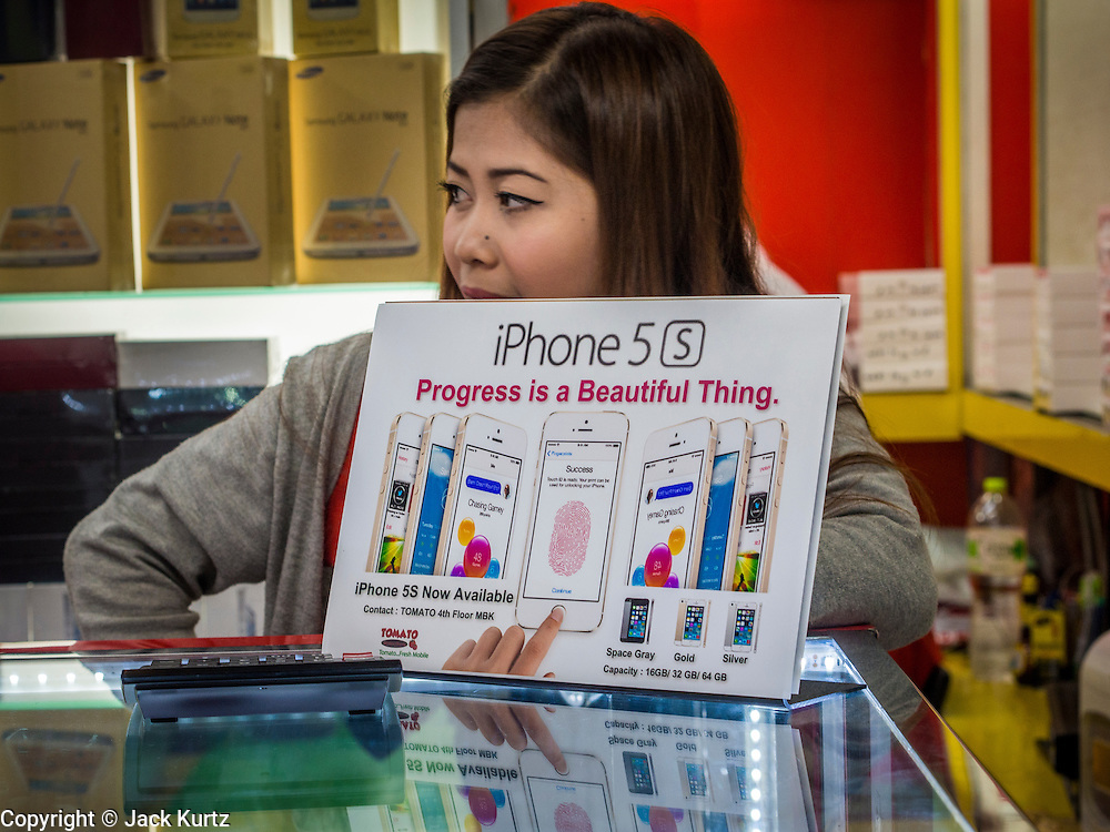 21 SEPTEMBER 2013 - BANGKOK, THAILAND: An electronics shop owner advertises that she has iPhone 5s models for sale in MBK in Bangkok. Customers around the world lined up Friday to pick up Apple's new flagship iPhone 5s and its lower cost, more colorful brother, the iPhone 5c. The phones went on sale in the US and select countries beyond the US on Friday. The iPhone 5s and iPhone 5c will not be officially released in Thailand until late 2013 but the phones are available through the unofficial grey market in MBK, a huge shopping complex in Bangkok with dozens of small electronics shops. Early purchasers in Thailand pay a premium for the new iPhones, the top of the line iPhone 5s with 64 gigabytes of memory is about 38,500Baht, more than $1,200 (US).      PHOTO BY JACK KURTZ